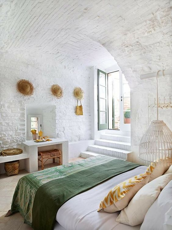 a mediterranean bedroom features whitewashed brick and tiles on the floor, everything is white except for bedding