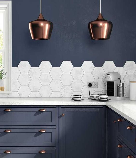 marble hexagon tiles and countertops stand out in this navy grey kithcne with copper accents
