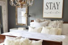 02 this guest bedroom features a vintage chandelier and a wall sconce for reading in bed