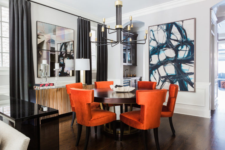 The dining area is bold and glam, there's a large artwork, a mirror, a brass and black chandelier and super colorful burnt orange chairs