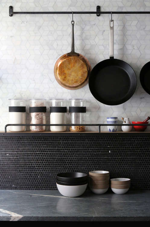 The kitchen backsplash is made with small black tiles, and the countertops are concrete