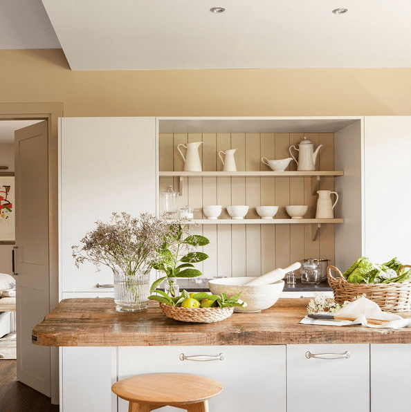 The kitchen has light-colored cabinets and rough wooden countertops