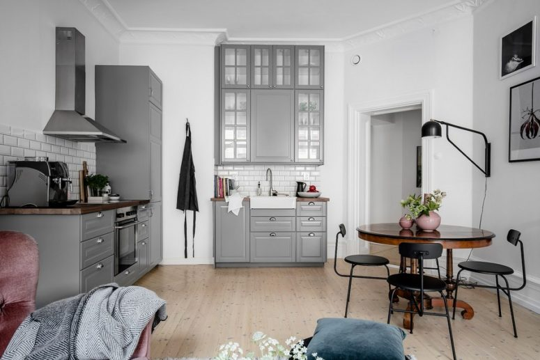 The kitchen is grey, with white subway tiles backsplashes and there's a small dining space with black chairs and a wooden table