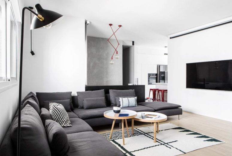 The living room features a large sectional grey sofa, a geo rug and eye-catchy red lights