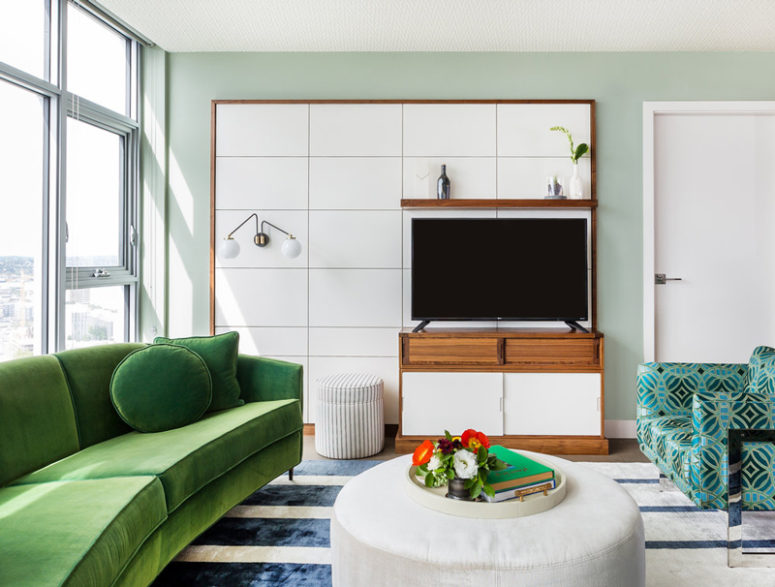 The living room is with stunning views, with an emerald sofa and bold turquoise printed chairs with mirror legs