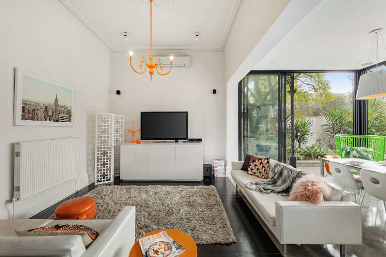 The living space features neutral furniture and decor and some bold orange touches