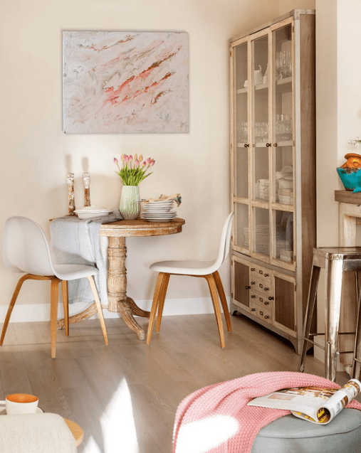This is a tiny dining space with a round wooden table, modern chairs and a glass cupboard