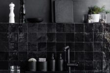 03 a bleached metal wall and a hand glazed glossy black tiles for a dark masculine kitchen