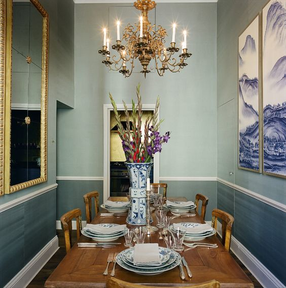 the dining room reminds of glaciers with greyish blue wallpaper and glacier artworks