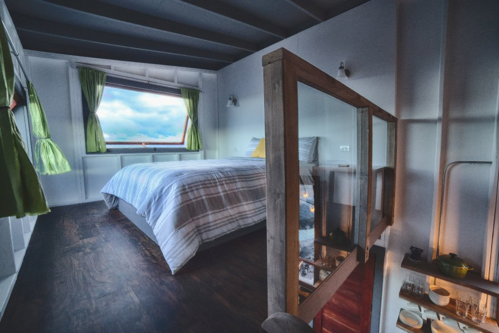 The bedroom features two windows to enjoy the views and a wooden railing with glass to make it separated yet not to cut the space
