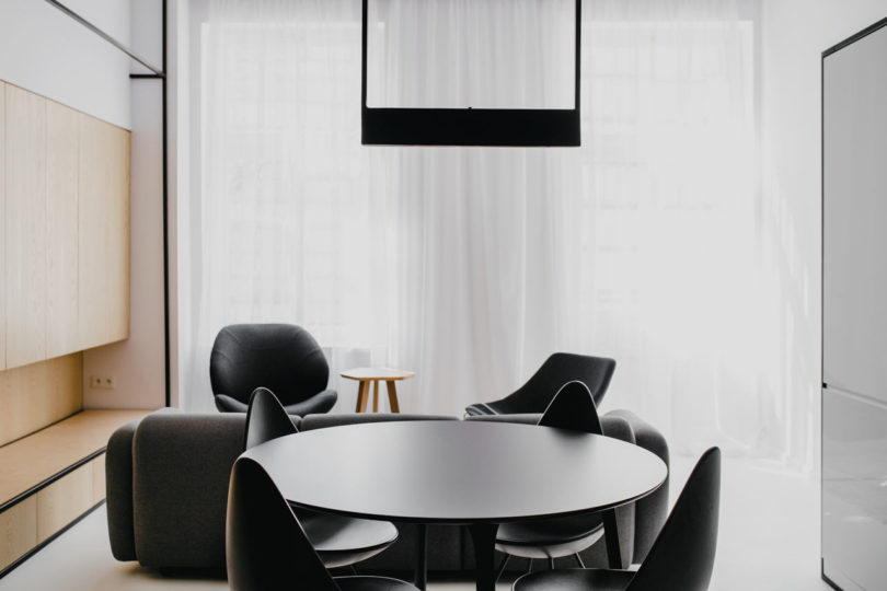 The dining area has a black dining set with a small round table, and wooden sleek cabinets on the left are for storage