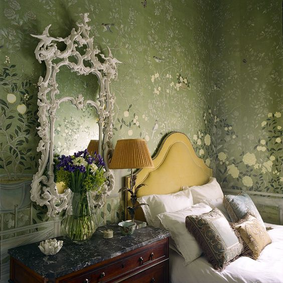 The guest room is luxurious with its 18th century mirror and an upholstered bed