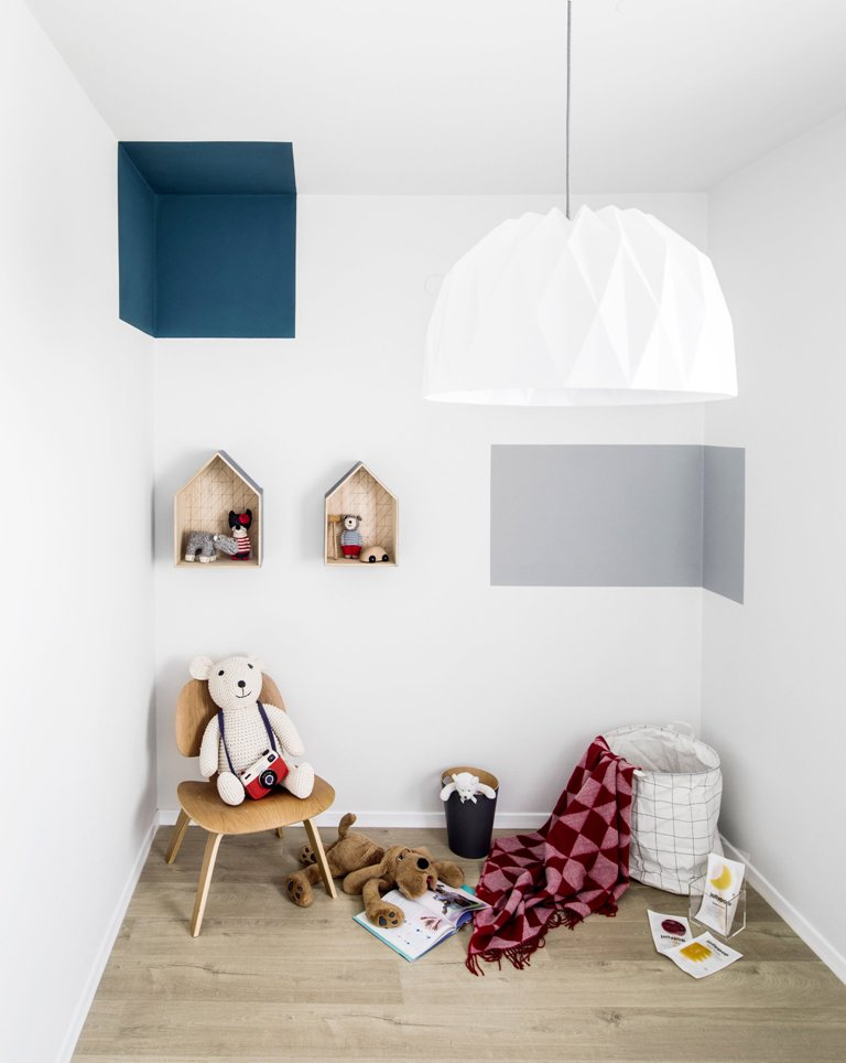 The kid's room features geometric prints, some toys and shouse shaped shelves on the wall