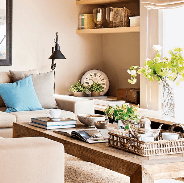 The living room is done in neutral beige tones, with a rustic wooden coffee table