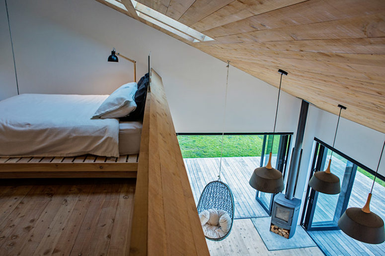 The master bedroom features a suspended bed, skylights on the sloping roof