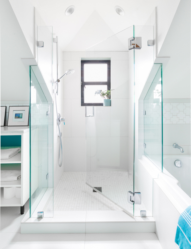 There's a shower with a small window, white tiles and glass doors, which is light-filled