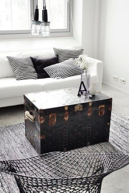 a Scandinavian room in black and white is ade more eye-catchy with a black vintage trunk, which serves as a coffee table