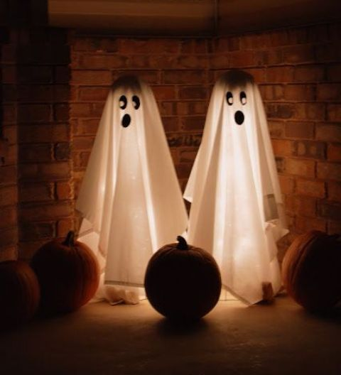 a couple of lit up ghosts with spooky faces and some pumpkins in the corner