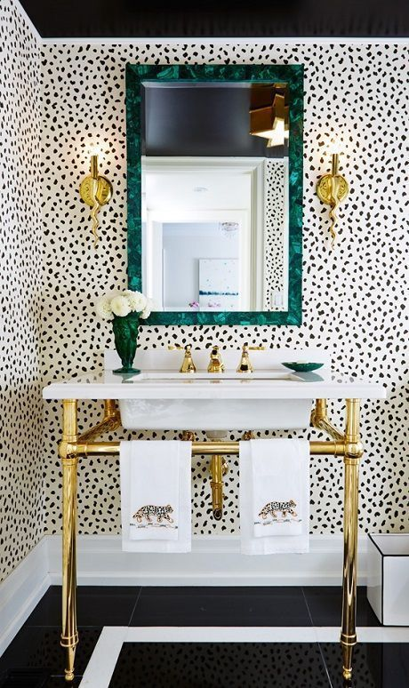 a glam powder room with dalmatian print wallpaper and brass accents