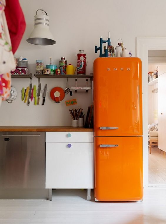 an eclectic kitchen with a bold orange Smeg fridge for a wow factor
