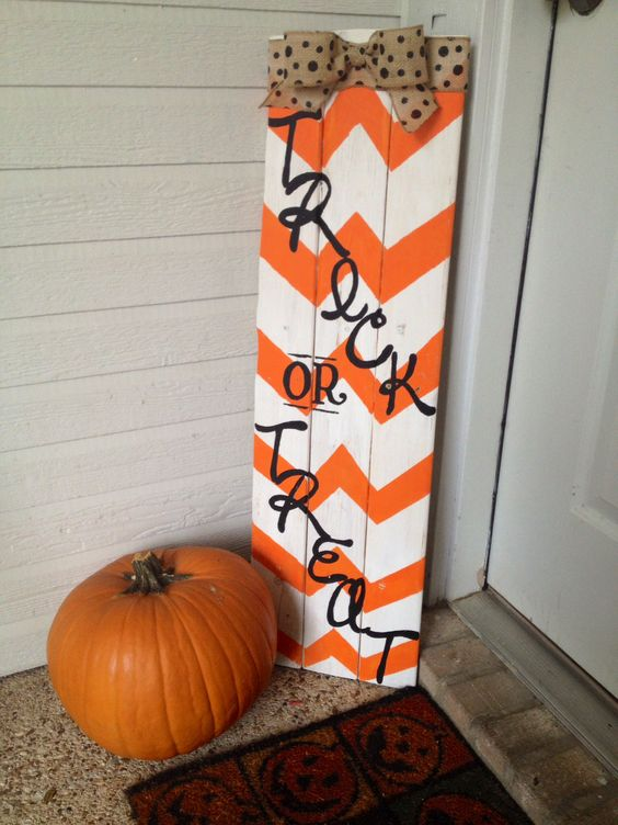 an orange and white chevron sign with black letters and a burlap bow