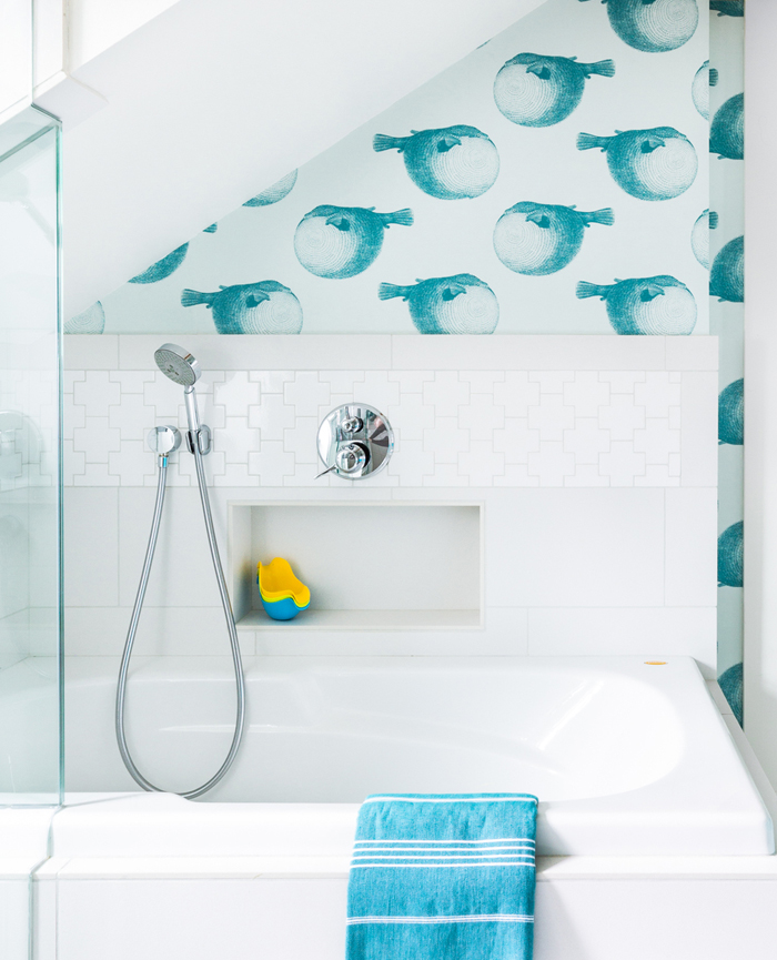 The bathtub is surrounded with white puzzle-shape tiles and there's a built-in shelf