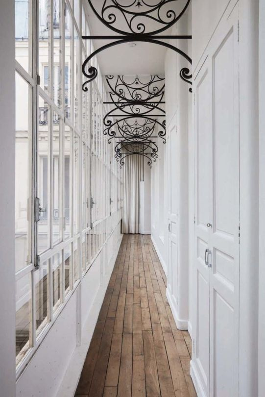 The corridor filled with light through the glazed wall is accentuated with forged vignettes on the ceiling