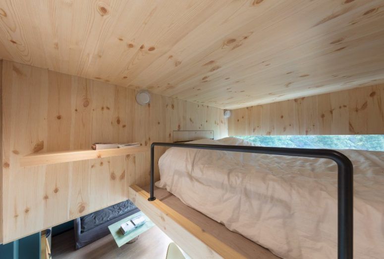 There's a mezzanine level up, which accomodates only a bed and a shelf, the owners feel like sleeping among the trees thanks to the window here