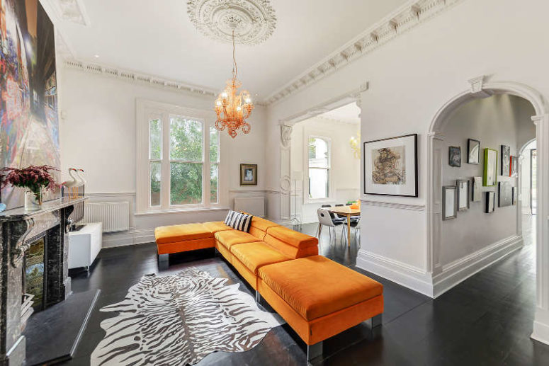 This room features bold orange furniture and an antique fireplace, a bold artpiece catches an eye