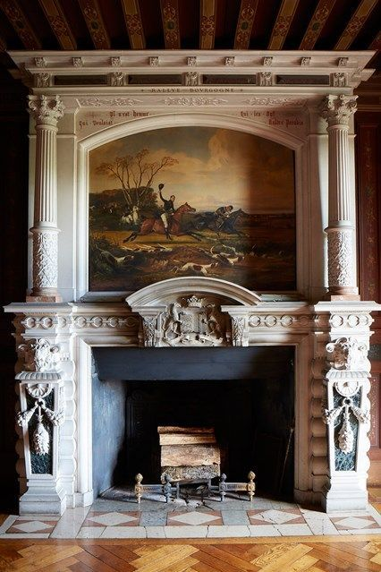a gorgeous antique fireplace with pillars and a painting, with firewood that can be burnt or not