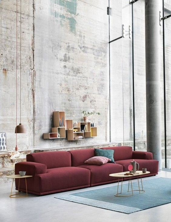 an industrial living room features a burgundy sofa and a muted blue rug for a contrast