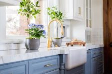 05 white suspended cabinets and dusty blue cabinets on the floor look lightweight and brass touches add chic