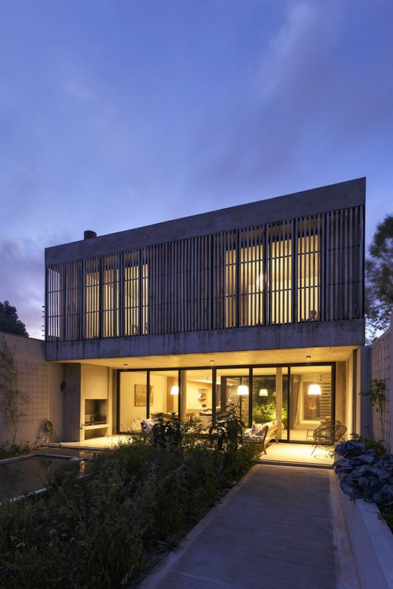 Full-height windows and sliding glass doors open the living spaces to the backyard