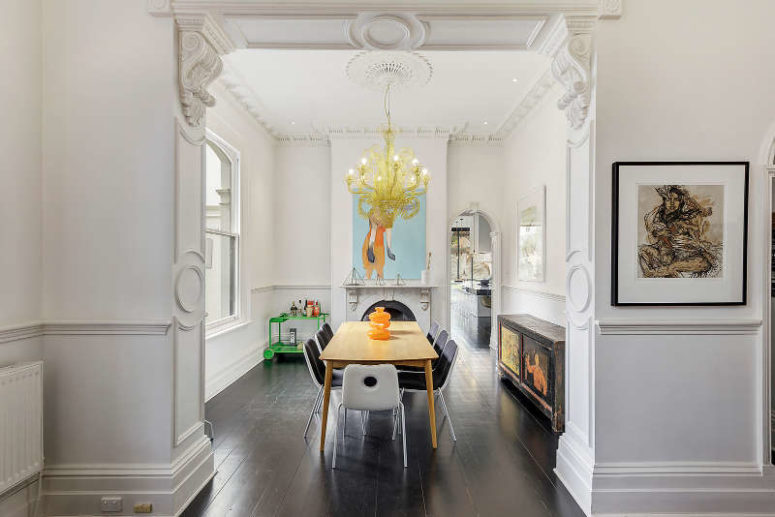 Here's a dining room with modern dinign furniture, an antique sideboard and a modern and bold chandelier