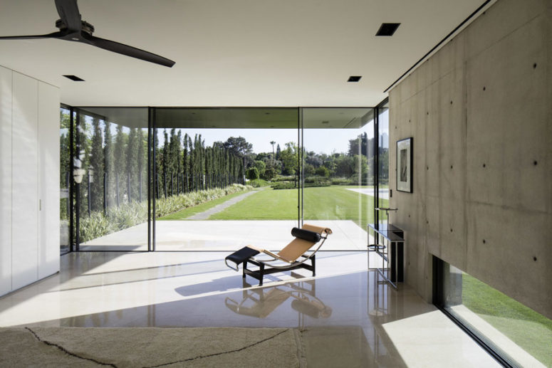 One of the walls is glass, with doors, which lead to the garden, and tall trees act as a living fence