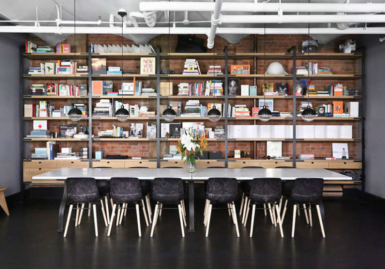 The dining space features large bookshelves that cover the whole wall, a long marble table and black chairs