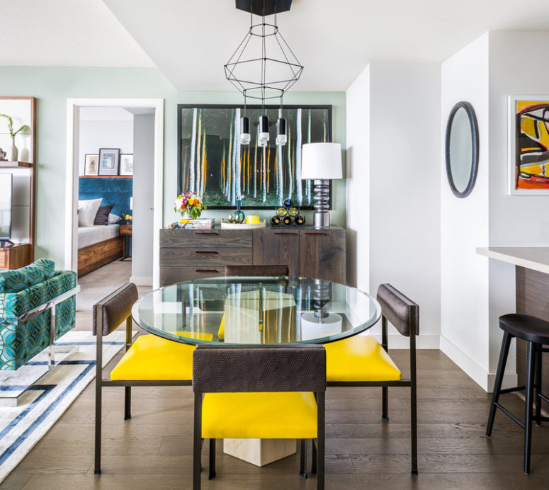 The dining zone has a glass table, yellow and brown chairs and a bold artwork