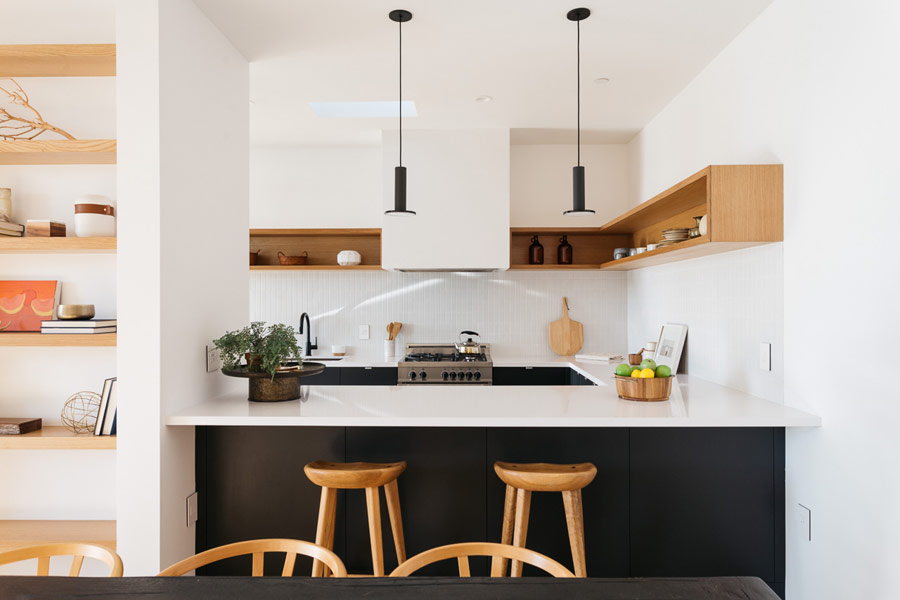 The kitchen has black cabinets and white countertops, this color scheme is used throughout the whole house