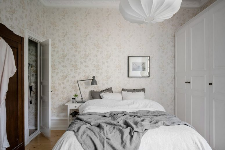 The master bedroom features neutral floral print wallpaper, a large comfy bed, wardrobes and wooden floors to create a cozy ambience