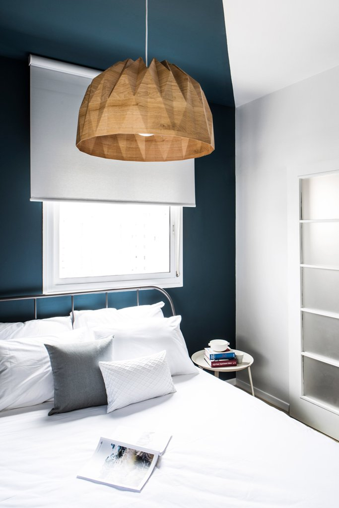 There's a large bed, a geo shaped wood lamp and a navy accent wall