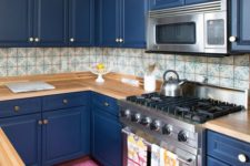 06 a bold blue kitchen with light-colored wooden countertops and a mosaic tile backsplash