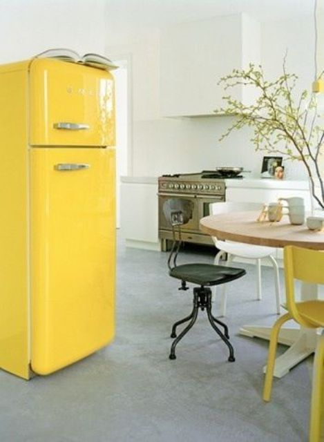 cheer up a neutral and peaceful kitchen with a sunny yellow Smeg fridge and a matching chair