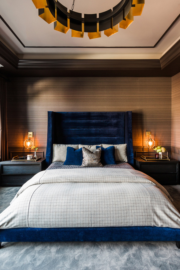 The master bedroom is moody and welcoming, with a blue velvet bed and art deco lamps