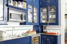 07 a bold blue kitchen with neutral countertops and brass handles for a vintage feel