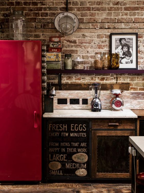 an industrial kitchen with a shiny red fridge to make a statement with color