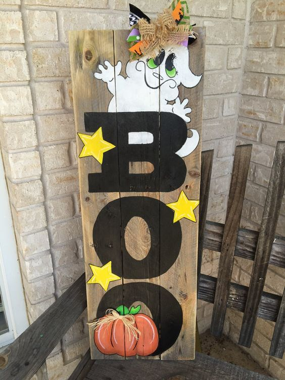 colorful BOO sign with yellow stars, a funky ghost, an orange pumpkin and some ribbon decor