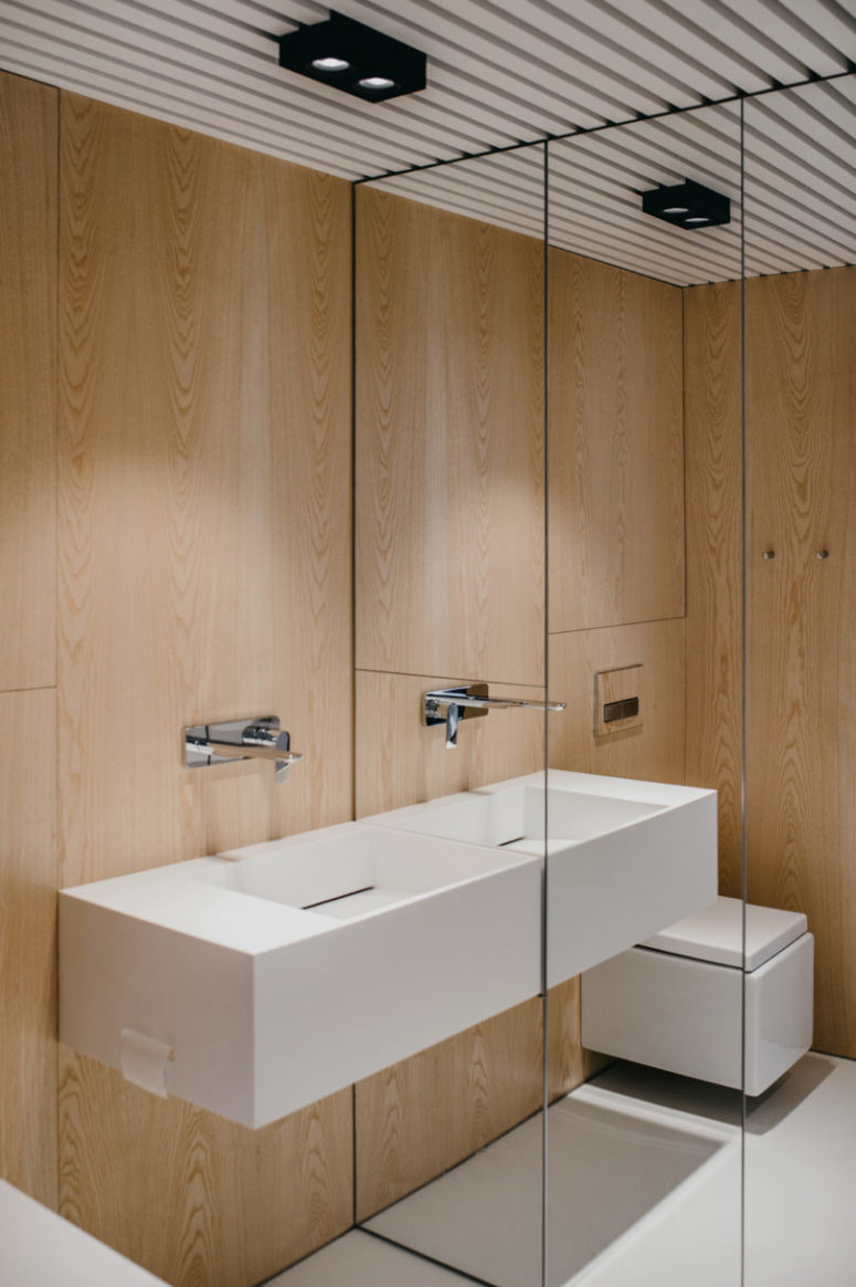 The bathroom is clad with light-colored wood, there's a mirror wall to make it look bigger