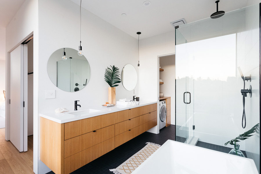 The bathroom is rather large, with a double vanity and a laundry space