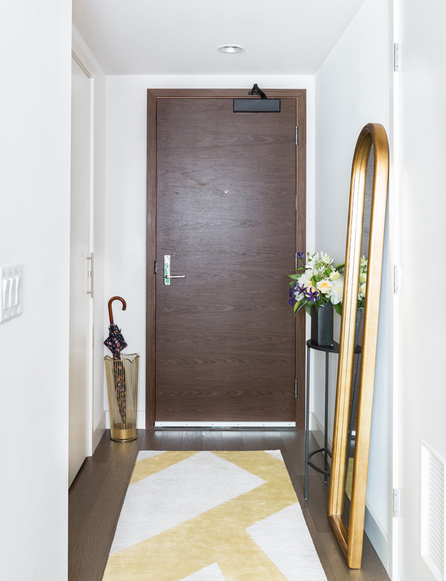 The entryway features a floor mirror, a geo rug and an umbrella stand