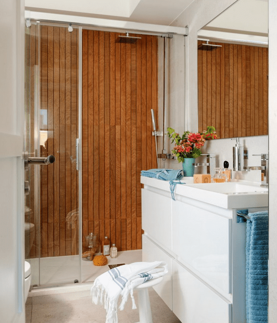 The mom's bathroom looks luxurious and modern, with a wood clad wall in the shower